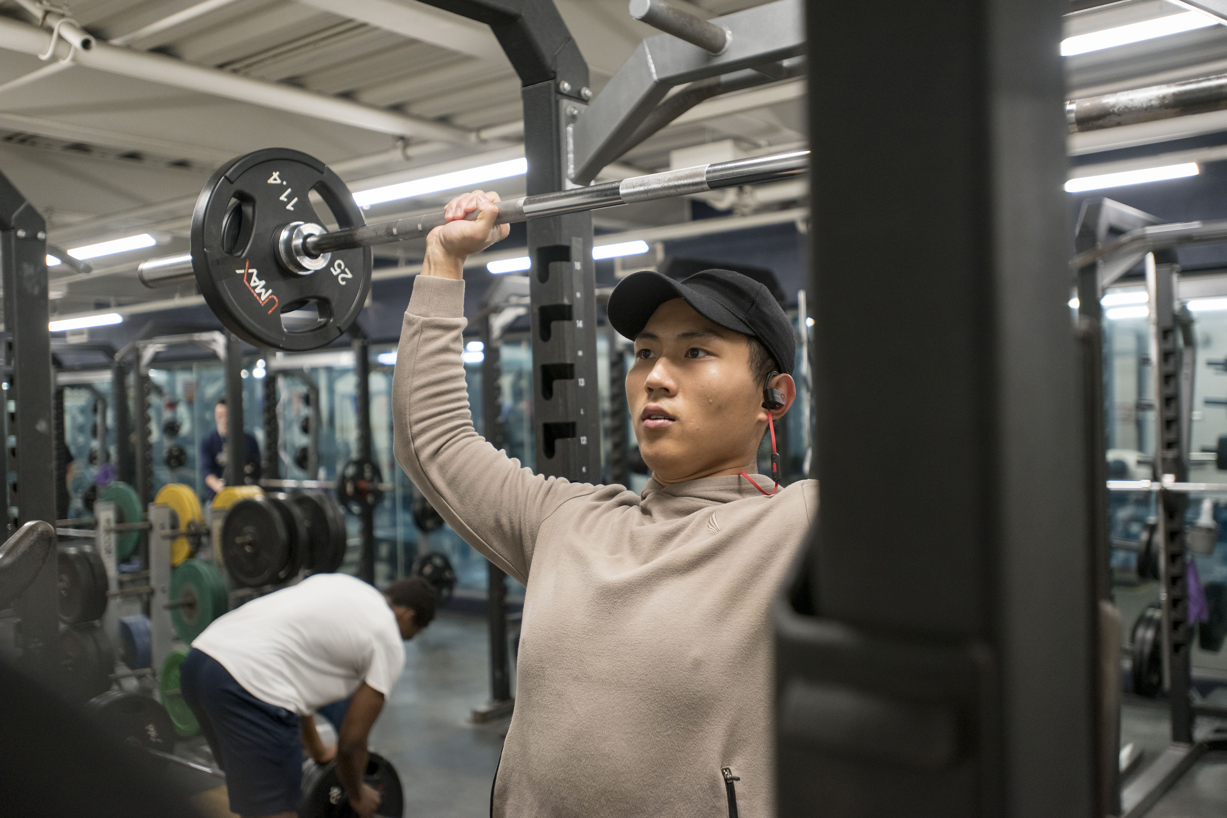International student Jiazhen Huang '18 (CLAS), a sport promotion major, lifts weights at the Student Recreational Facility on Feb. 22, 2018. (Sean Flynn/UConn Photo)