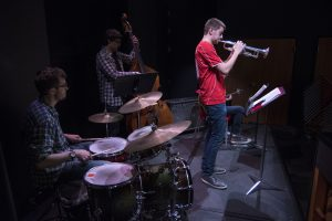 """From left, Steven McArdle on drums, Nathan Giordano on bass, and Grant Eagleson on trumpet, all senior music majors, play at """"Jazz Night at the Ballard."""" (Garrett Spahn '18 (CLAS)/UConn Photo)"""