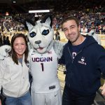 Ryan and Laura Marcoux pose for a picture with the Husky mascot while attending a women's basketball game in Gampel Pavilion during their recent visit to Storrs. (Stephen Slade '89 (SFA) for UConn)