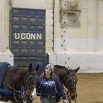 Sage Saffran '19 (CAHNR), an animal science major, walks two polo ponies (as the horses are known) before the UConn Men's and Women's Polo Match versus Kentucky on Feb. 3, 2018. The door with the legend UConn represents the goal. (Garrett Spahn '18 (CLAS)/UConn Photo)