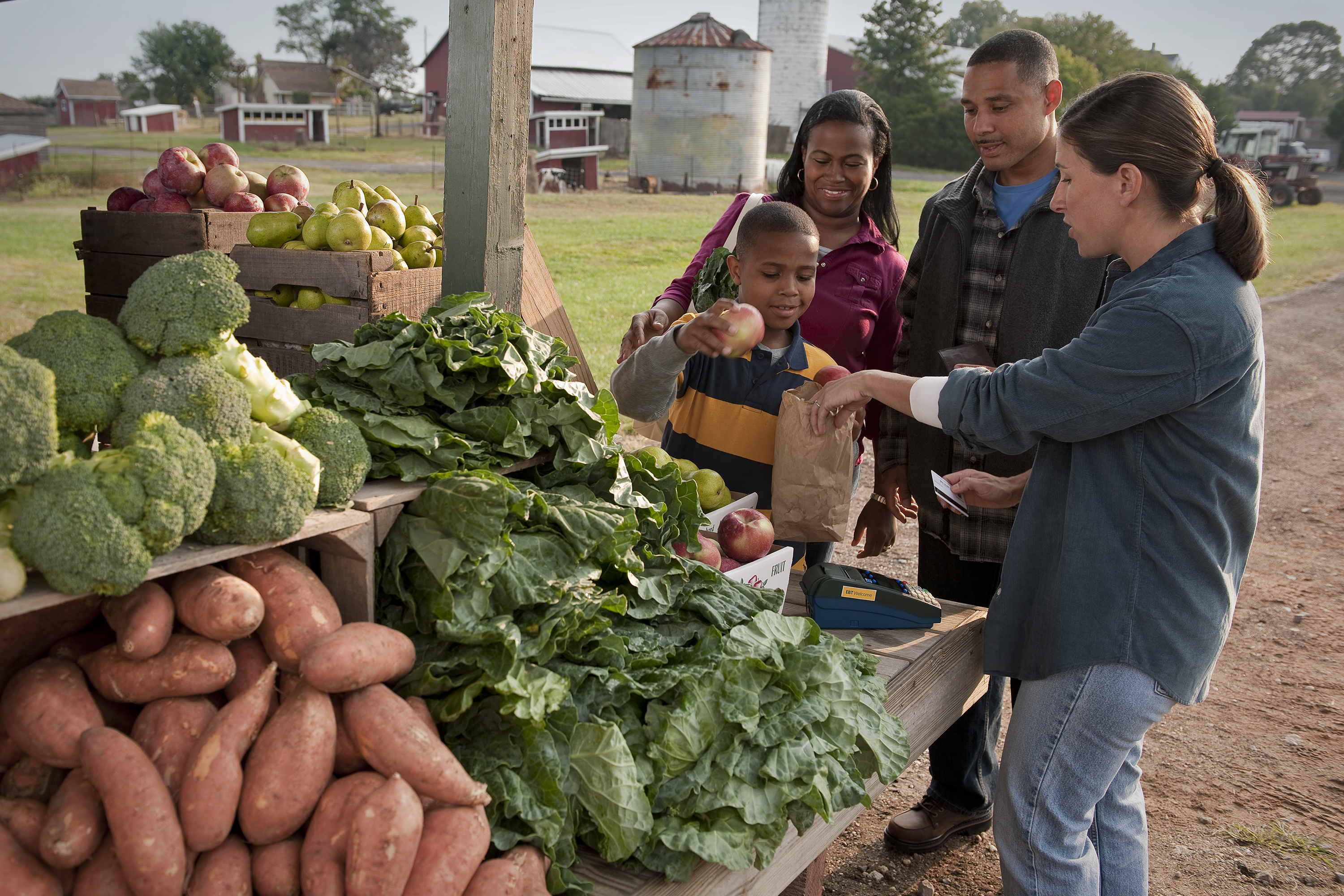 A family purchases produce from a farmers market vendor. (SNAP-Ed Photo Gallery, USDA)