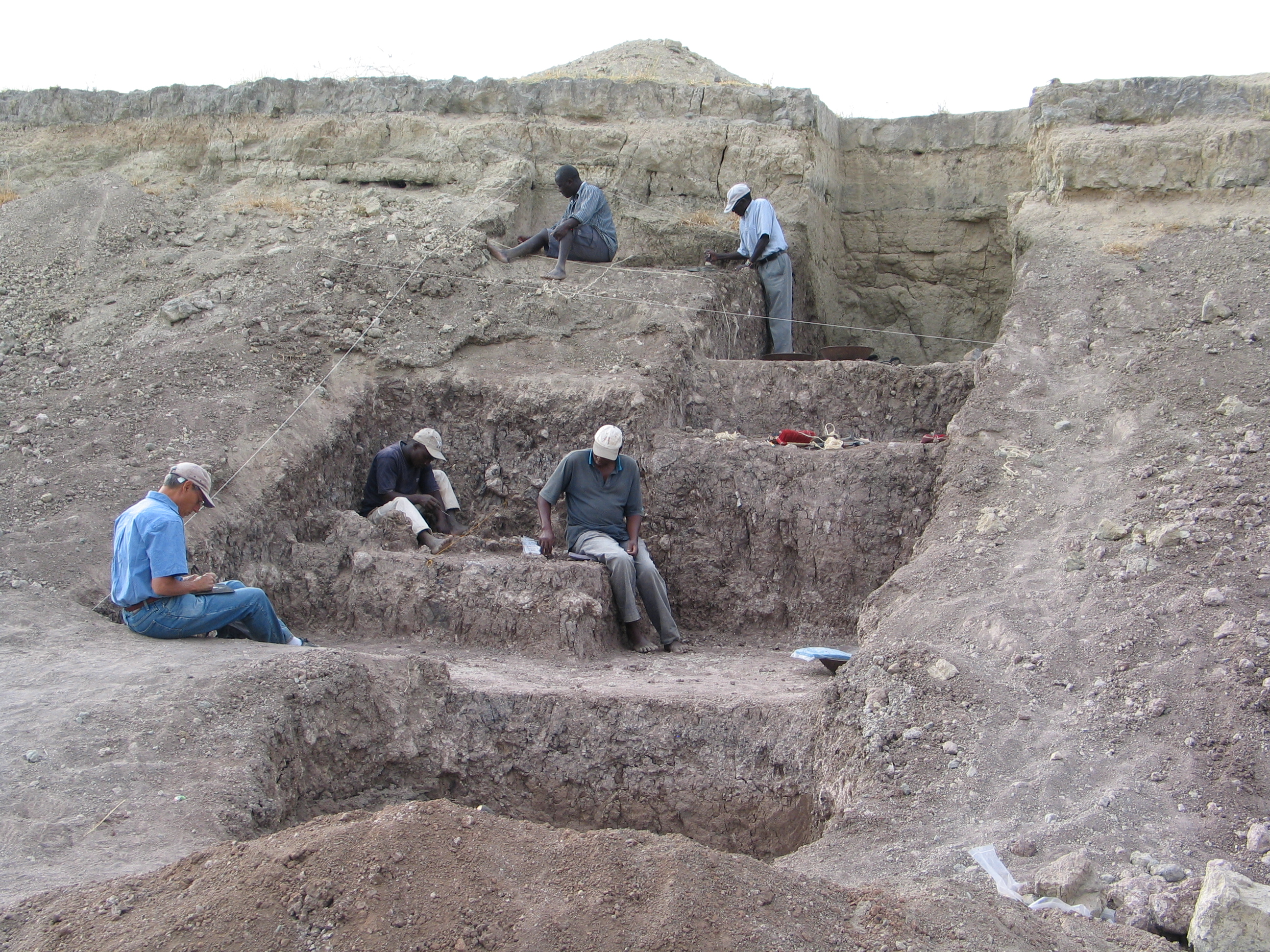 In this Olorgesailie Basin excavation site, red ocher pigments were found with Middle Stone Age artifacts. The light brown and gray layers provide evidence of ancient soils and of landscapes affected by earthquakes and other seismic activity, factors that rapidly altered the environment and resources on which human ancestors depended for survival. (Human Origins Program, Smithsonian)