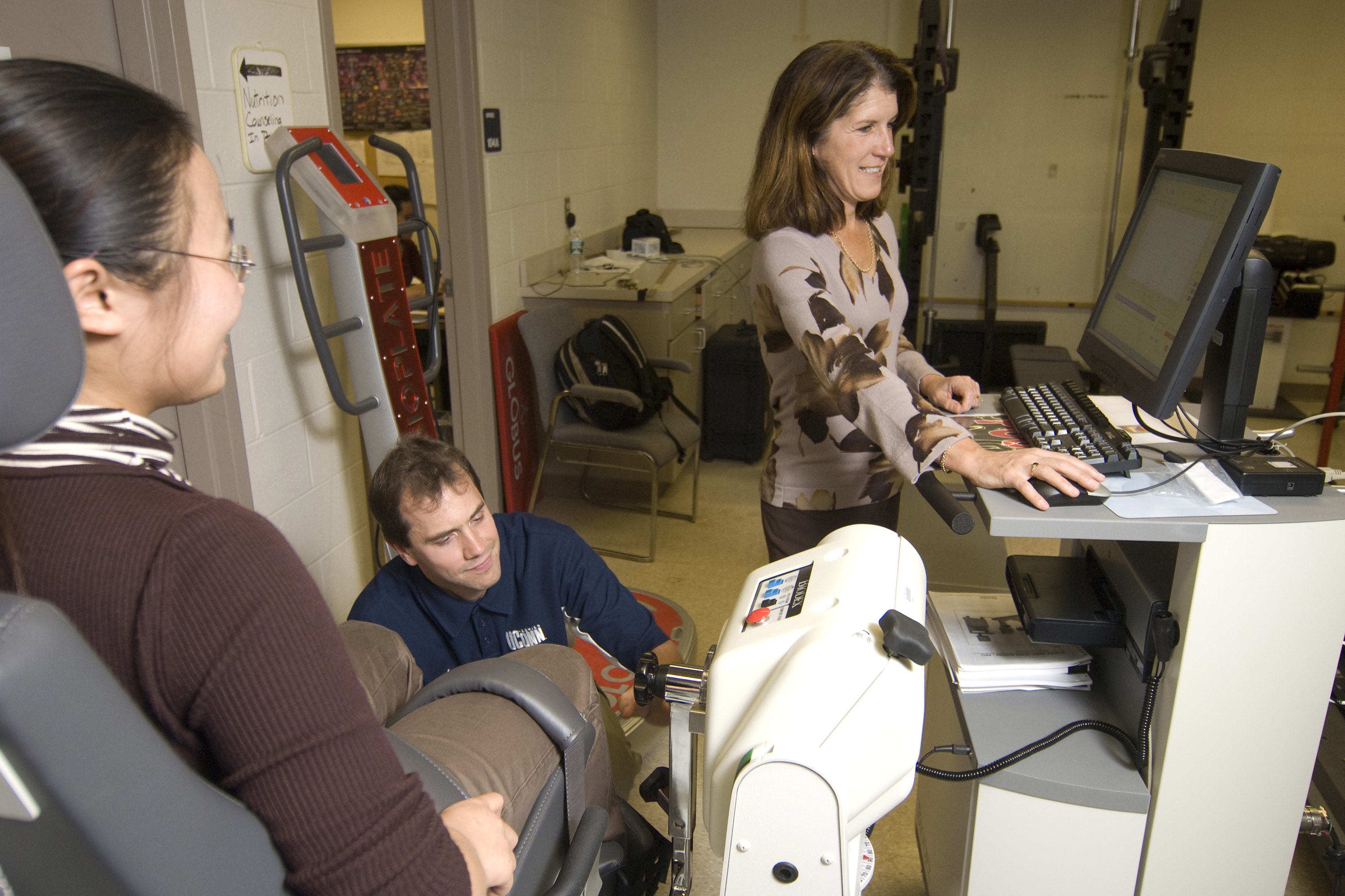 Linda Pescatella (back center), professor of kinesiology, and Matthew Kostek, graduate assistant in kinesiology, (front left), analyze a student attached to a Biodex machine in a lab in the Kinesiology department.