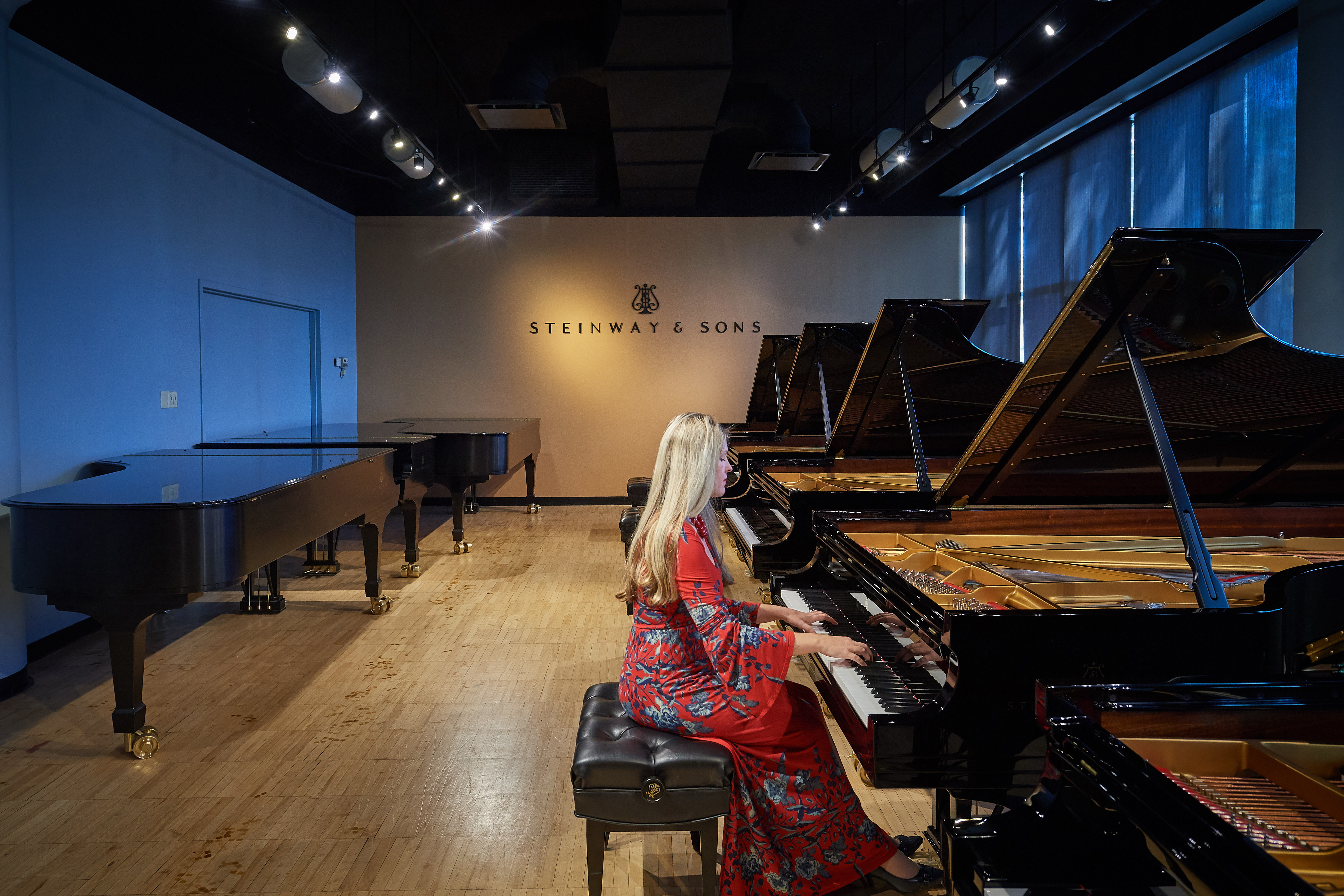 Angelina Gadeliya, assistant professor-in-residence and director of keyboard studies, tests grand pianos at the Steinway & Sons factory in Queens, New York, last October. (Peter Morenus/UConn Photo)