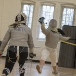 Freshman Michelle Martinez '21 (CAHNR), right, practices a move with senior Joanna Scuteri '18 (CLAS), a geoscience major. All fencers require a jacket, a mask, a glove, trousers or knickers, white stockings, flat-soled shoes, a body cord, and a weapon. (Garrett Spahn '18 (CLAS)/UConn Photo)