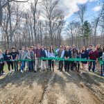Richard Miller, director of the Office of Environmental Policy, prepares to cut the ribbon at the dedication of the new trailhead to the Hillside Environmental Education Park on April 26, 2018. (Peter Morenus/UConn Photo)