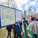 A group hike follows the reopening of the Hillside Environmental Education Park trail near the Innovation Partnership Building. (Peter Morenus/UConn Photo)