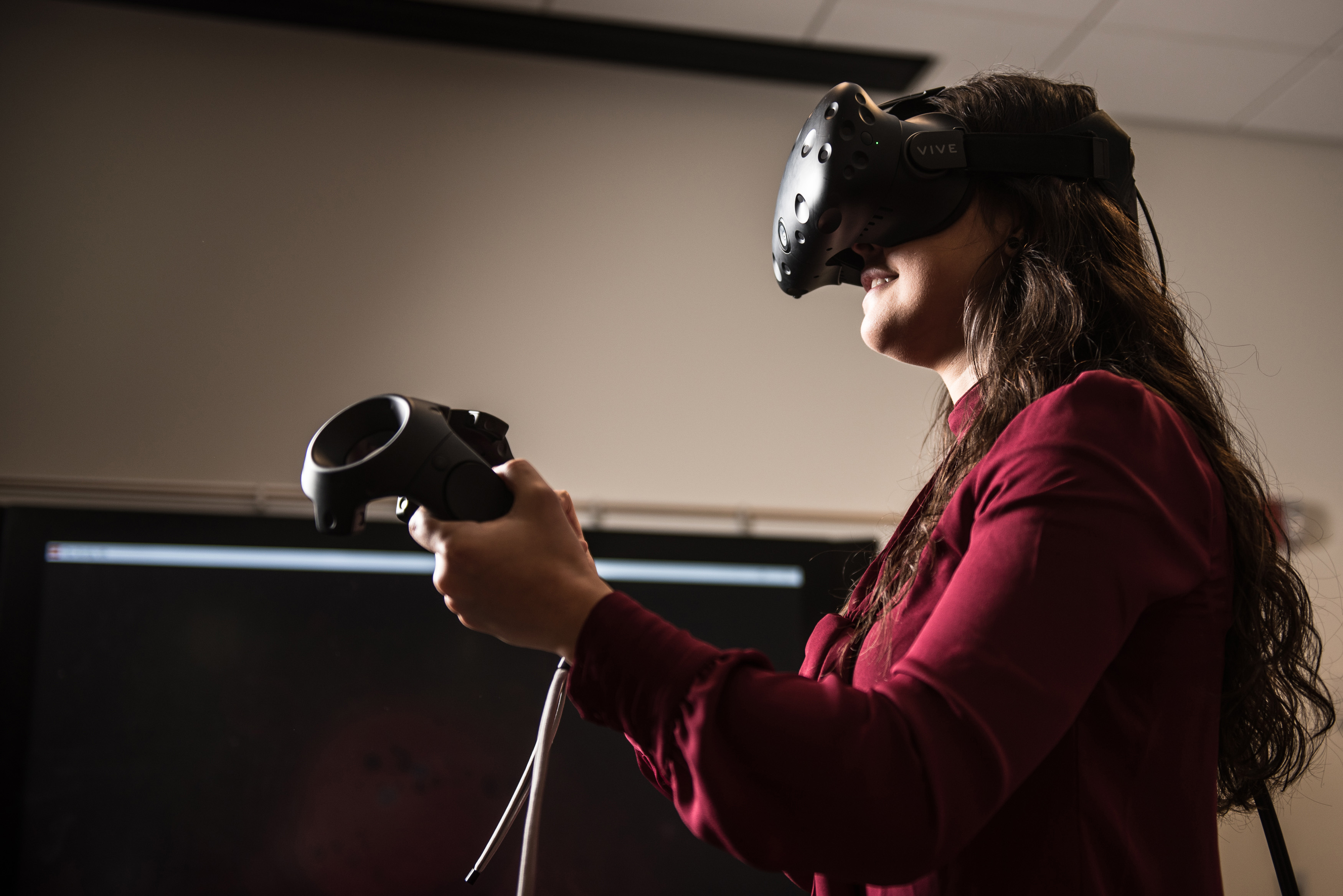 With a virtual reality headset on, junior Carina Zamudio '19 (CLAS) spent part of a Friday afternoon trying to slay villains who were intent on breaching the security around a virtual castle. (Nathan Oldham/UConn School of Business Photo)
