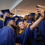 Bliss Dasilva '10 (CAHNR), '18 (NUR) takes a selfie with classmates at the Carolyn Ladd Widmer Wing of Storrs Hall before the start of the School of Nursing Commencement procession on May 5. (Peter Morenus/UConn Photo)