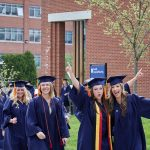 With arms raised, Sydney Gagne '18 (NUR), left, and Molly Gaffney '18 (NUR) walk along Glenbrook Road during the School of Nursing Commencement procession. (Peter Morenus/UConn Photo)