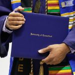 A degree candidate holds a diploma case during the School of Engineering Commencement ceremony. (Peter Morenus/UConn Photo)
