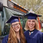 Courtney Dawless '18 (ENG), left, and Amanda Giroux '18 (ENG) pose for a photo with a UConn bus following the School of Engineering Commencement ceremony. (Peter Morenus/UConn Photo)