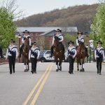 The UConn Morgan Drill Team leads the the College of Agriculture, Health, and Natural Resources Commencement procession along Hillside Road. (Peter Morenus/UConn Photo)