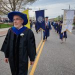 Headley Freake, professor of nutritional sciences, leads the banners during the College of Agriculture, Health, and Natural Resources Commencement procession along Hillside Road. (Peter Morenus/UConn Photo)