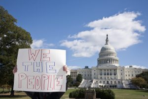 A protester holding a placard saying 'We The People' in front of the U.S. Capitol Building. (Getty Images)