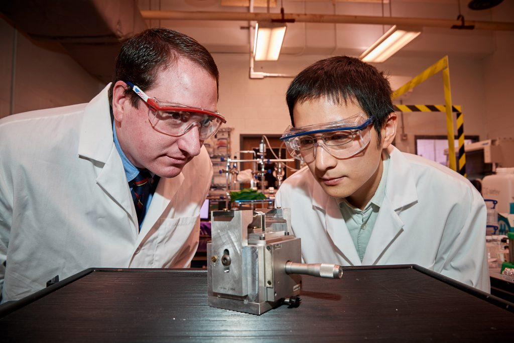 Michael Pettes, left, assistant professor of mechanical engineering, and Ph.D. student Wei Wu check a specially engineered device they created to exert strain on a semiconductor material only six atoms thick, on April 18, 2018. (Peter Morenus/UConn Photo)