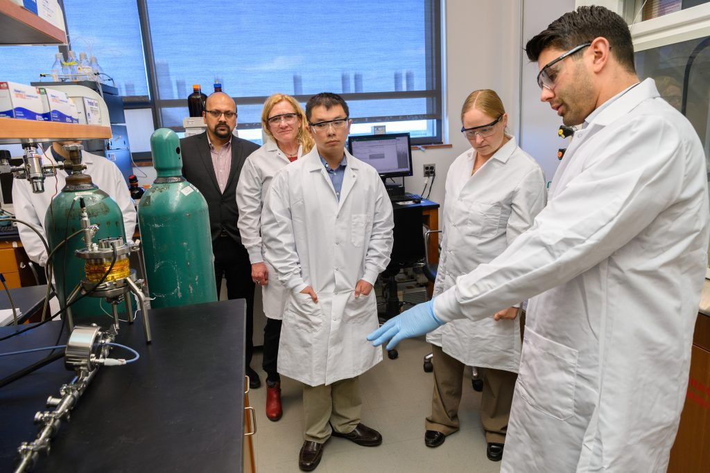Antonio Costa, assistant research professor of pharmaceutical science, right, explains the apparatus for continuous processing of liposome drug products at the Pharmacy/Biology Building. From left are Bodhi Chaudhuri, associate professor of pharmacy, Diane Burgess, Board of Trustees Distinguished Professor of Pharmaceutics, and Katherine Tyner and Su-Lin Lee, both of the FDA's Office of Pharmaceutical Quality. (Peter Morenus/UConn Photo)