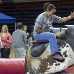 Angie Reyes of University Communications rides a mechanical bull during Employee Appreciation Day on May 10. (Sean Flynn/UConn Photo)