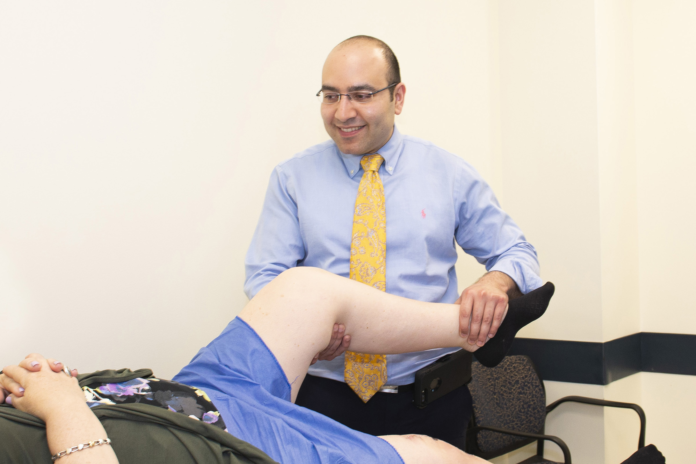 Dr. Mo Halawi examines a patient. Halawi is an orthopedic surgeon specializing in joint reconstructive surgery who joined UConn Health last fall and is spearheading same-day release for joint replacement patients. (Kristin Wallace/UConn Health Photo)