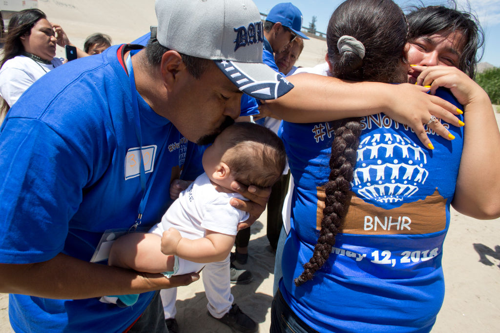 Migrant families embrace at the border between El Paso, Texas, and Juarez, Mexico. (Photo by Andrew Lichtenstein/Corbis via Getty Images)
