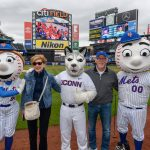 President Susan Herbst and her husband Doug Hughes pose for a photo with Mrs. Met, Jonathan the Husky, and Mr. Met before the New York Mets baseball game on June 3, 2018. (Peter Morenus/UConn Photo)