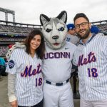 Sandra Francese, right, of Stamford, and Brian Francese '06 (BUS) with Jonathan the Husky at a New York Mets baseball game at Citi Field in Queens New York on June 3, 2018. (Peter Morenus/UConn Photo)