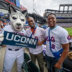Merlon Pinnock '15 MBA, center, and Oneil McCaulsky, both of Poughkeepsie New York with Jonathan the Husky at a New York Mets baseball game at Citi Field in Queens New York on June 3, 2018. (Peter Morenus/UConn Photo)