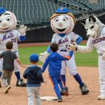 Jonathan the Husky, right, gives high fives to children during the Mr. Met Dash following a New York Mets baseball game at Citi Field in Queens New York on June 3, 2018. (Peter Morenus/UConn Photo)