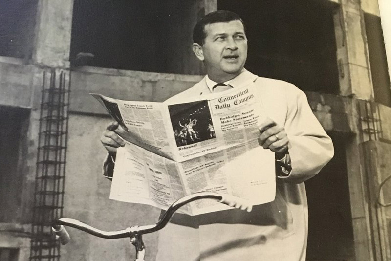 UConn President Homer Babbidge holds up a copy of the Daily Campus. It was one of the photos included in a picture essay titled 'The Odyssey of Homer' in the Nutmeg Yearbook of 1972, the year Babbidge stepped down. (Nutmeg Yearbook Photo)