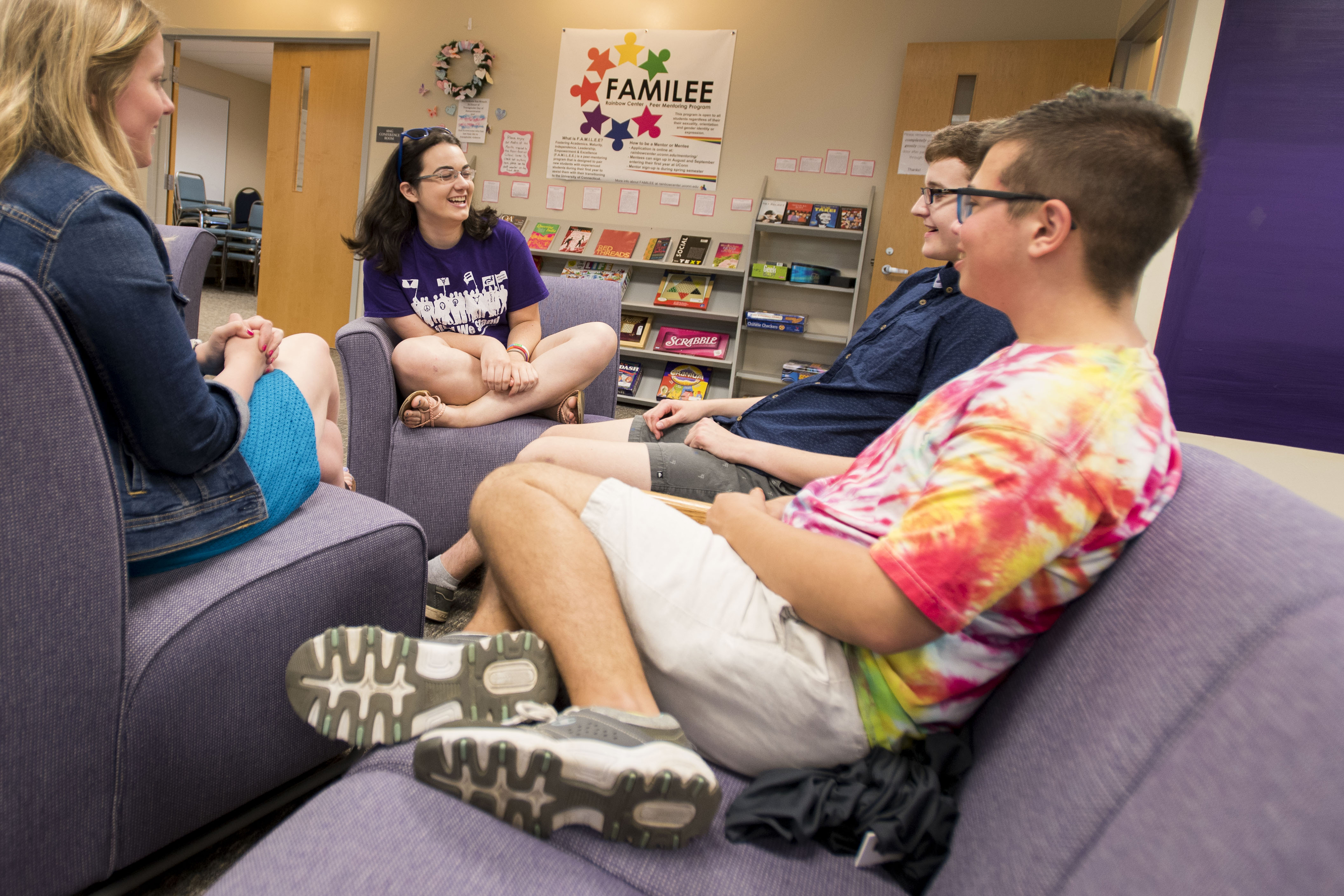 Clockwise from left, program coordinator Julia Anderson '18 MA has a conversation with Anastasia Martineau '20 (CLAS), Emmett Santisi '21 (ENG), and Zane Carey '18 (CLAS) at the Rainbow Center on June 18, 2018. (Sean Flynn/UConn Photo)