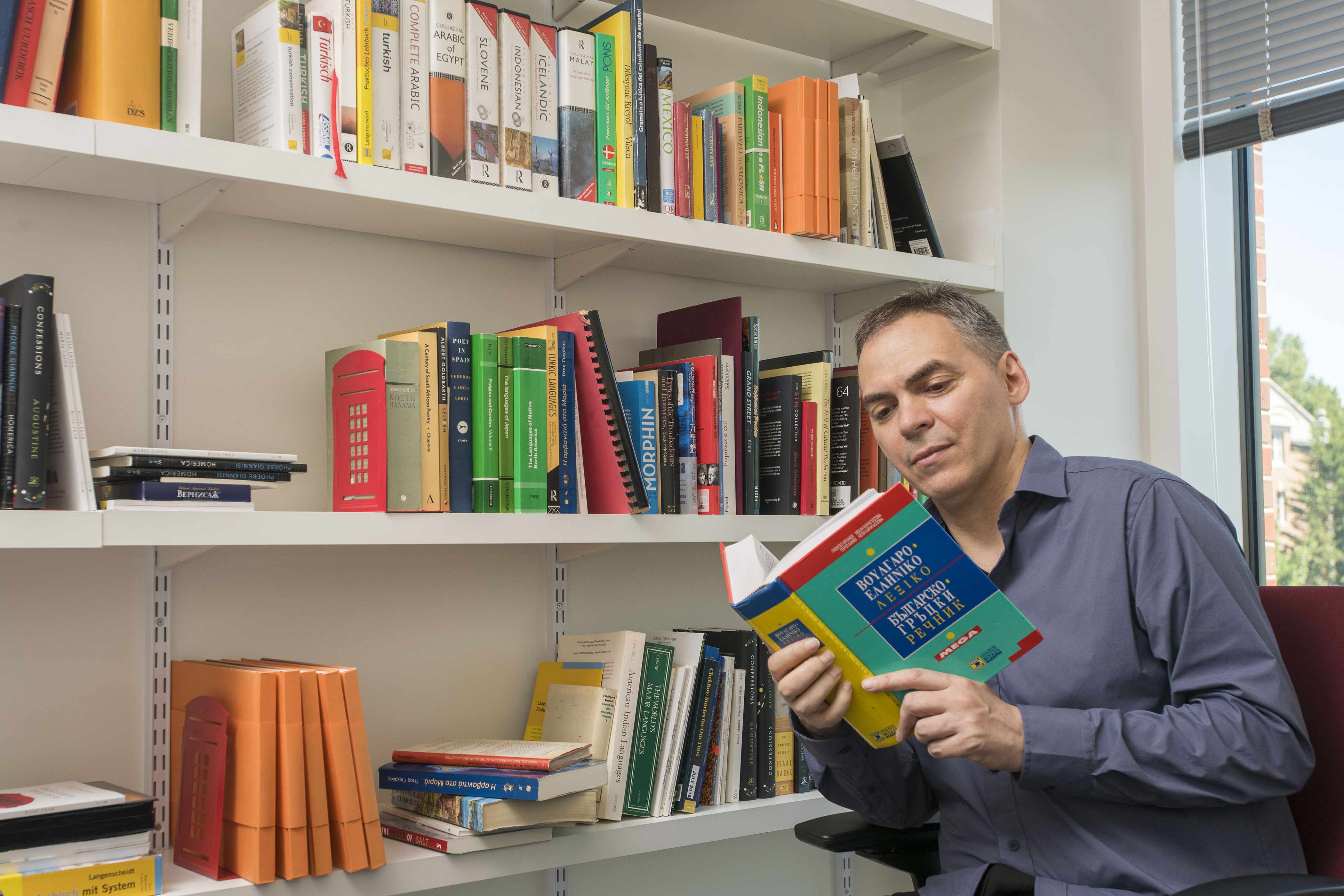 Translation expert Peter Constantine consults a Greek dictionary from the collection of the Department of Literatures, Cultures, & Languages. (Sean Flynn/UConn Photo)