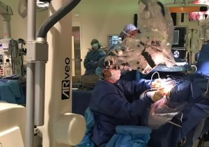 Skull-based surgery team at UConn Health is the first in the country to utilize novel ARveo microscope. with augmented reality capabilities. Dr. Dan Roberts (seated) doing his part of the complex skull-based surgery with Dr. Ketan Bulsara this July.