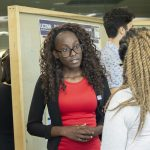 Venoude Valmyr, a biomedical engineering major in the School of Engineering with a minor in anthropology, speaks about her research at the McNair Scholars Poster Session on July 25, 2018. (Christine Buckley/UConn Photo)