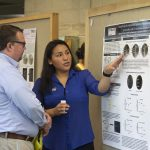 Sthefany Calle, a molecular and cell biology major in the College of Liberal Arts and Sciences, speaks about her research at the McNair Scholars Poster Session on July 25, 2018. (Christine Buckley/UConn Photo)