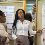 Kerryann Ashley, a molecular and cell biology major in the College of Liberal Arts and Sciences, speaks about her research at the McNair Scholars Poster Session on July 25, 2018. (Christine Buckley/UConn Photo)