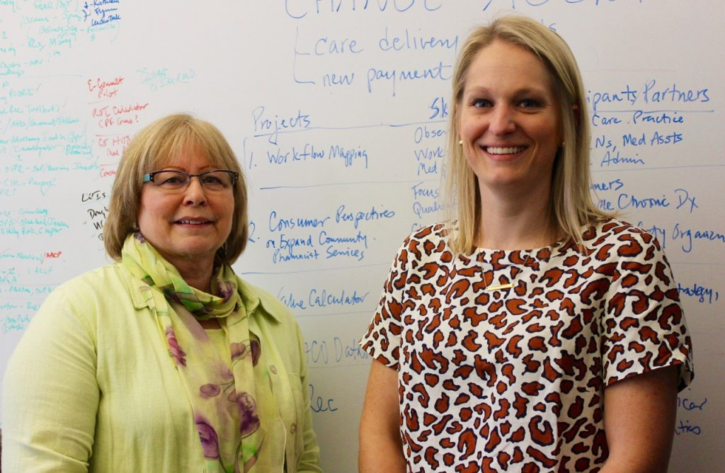 Marie Smith and Katherine Steckowych in front of white board.