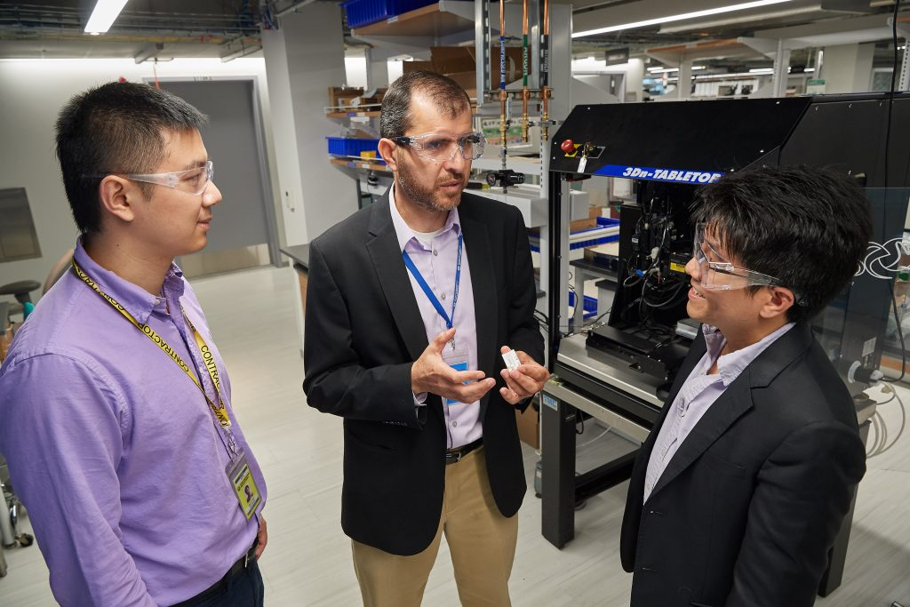 Sameh Dardona, center, principal research engineer and associate director, United Technologies Research Center, with Anson Ma, associate professor of chemical and biomolecular engineering, right, and Alan Shen, a Ph.D. student, look at a prototype wear sensor at the UTC Research Center in East Hartford on June 18, 2018. (Peter Morenus/UConn Photo)