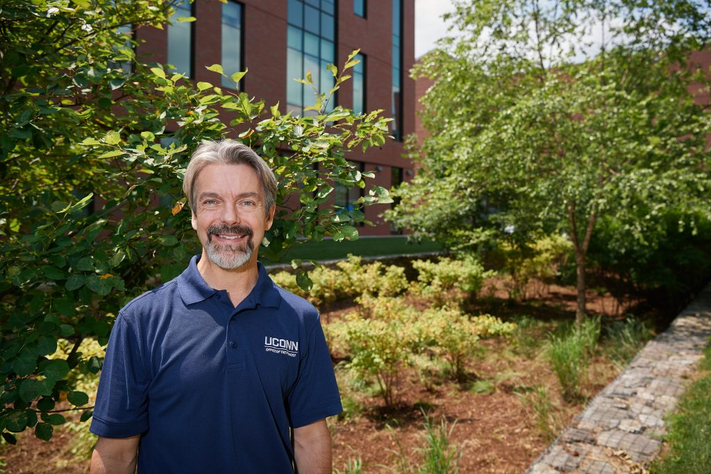 John Volin, vice provost for academic affairs and professor of natural resources and the environment, stands near a bioretention swale outside behind McHugh Hall on July 11, 2018. (Peter Morenus/UConn Photo)