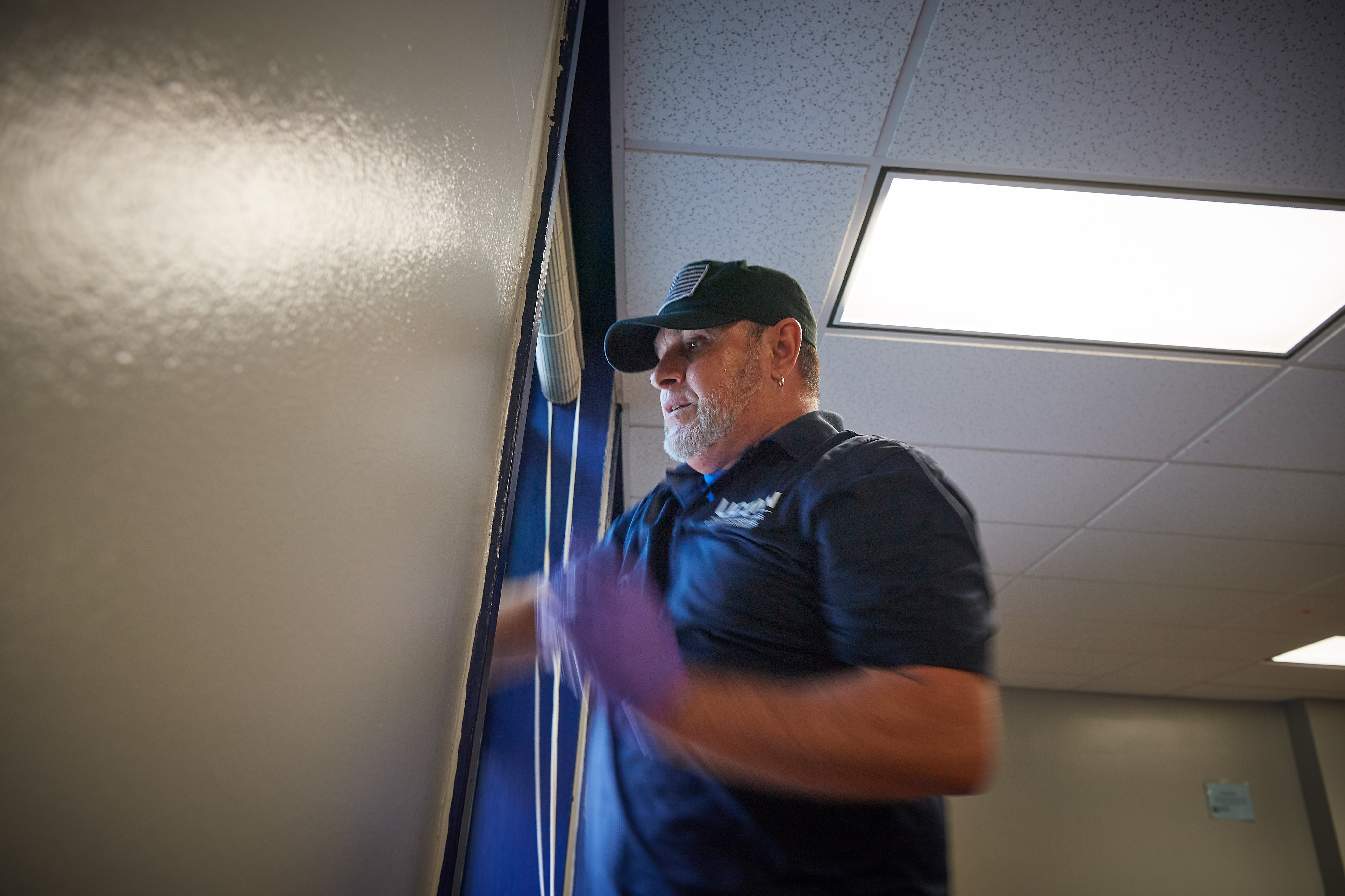 Lesme Valentin, a university custodian, cleans windows in a second floor lounge at Belden Hall onAug. 16, 2018. (Peter Morenus/UConn Photo)