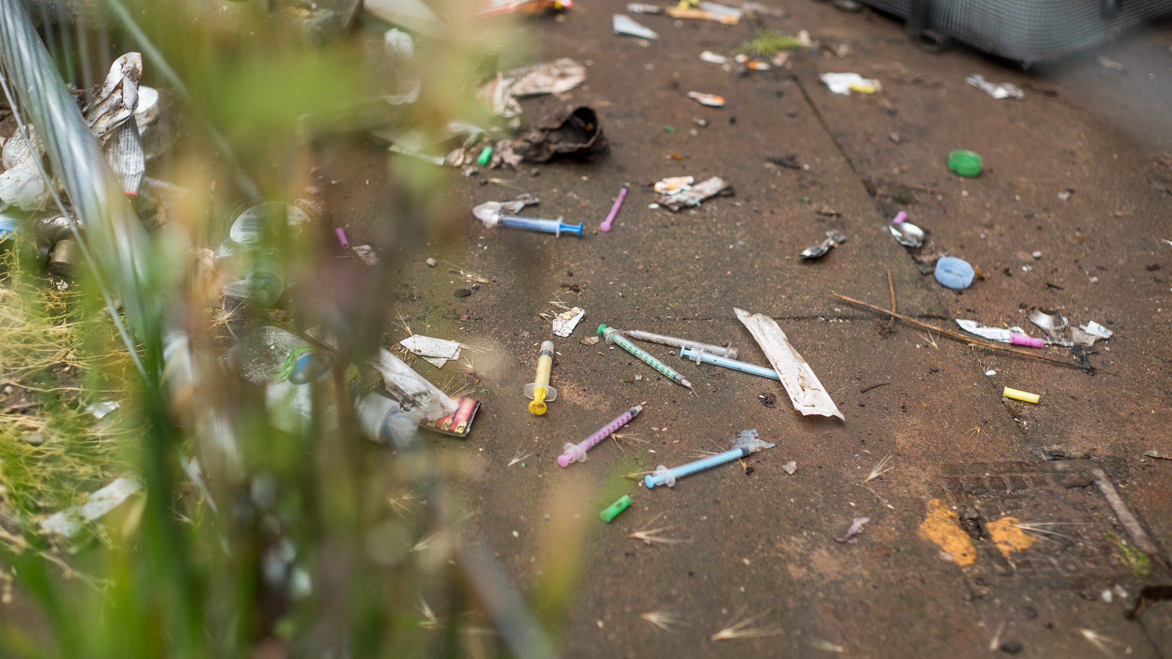 Syringes scattered on a litter strewn pavement. (Getty Images)
