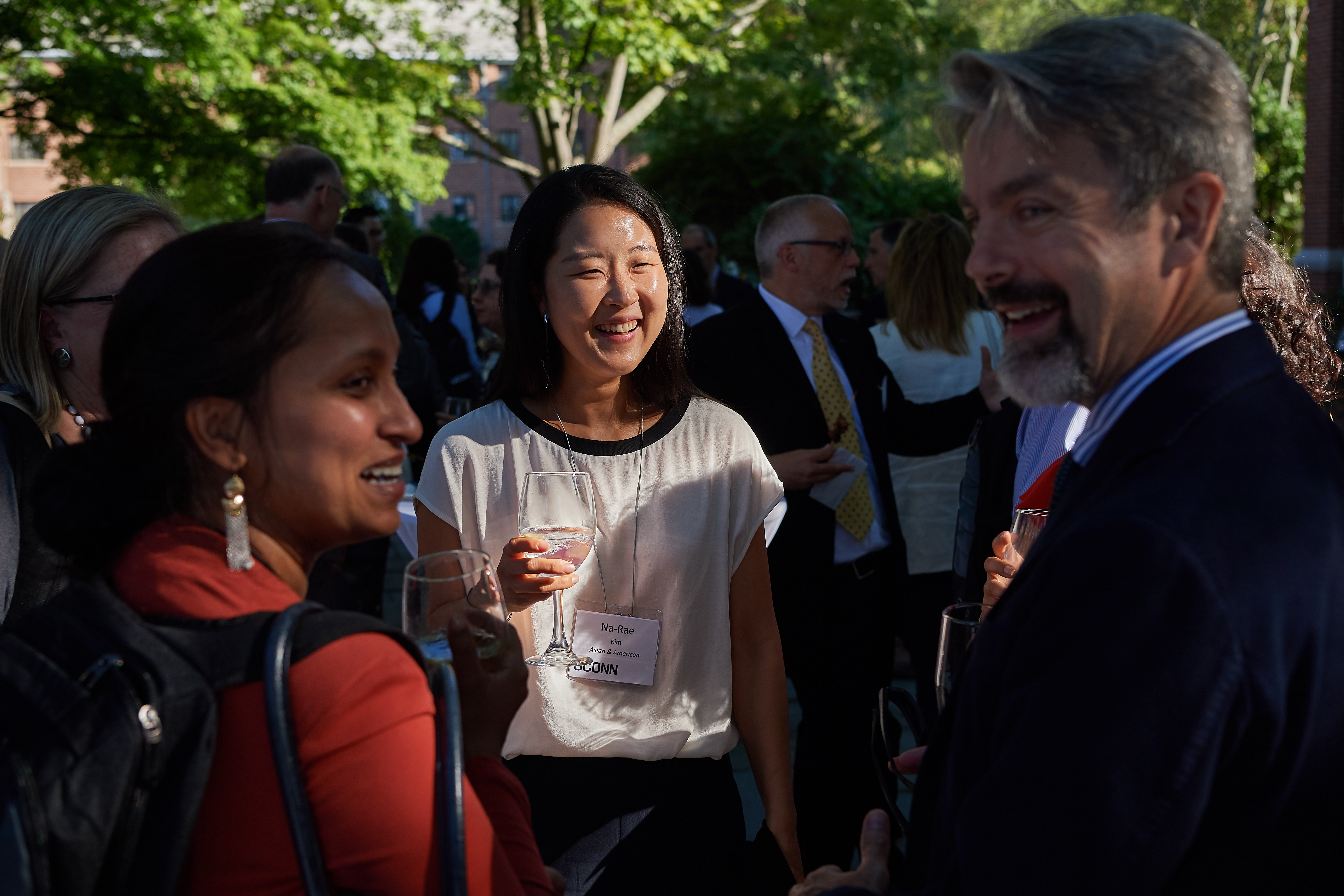 Na-Ree Kim, center, assistant professor in residence of Asian and Asian-American studies, Rupal Parekh, left, assistant professor of social work,and John Volin, vice provost for academic affairs speak at a reception following new faculty orientation on the patio of the William Benton Museum of Art. (Peter Morenus/UConn Photo)
