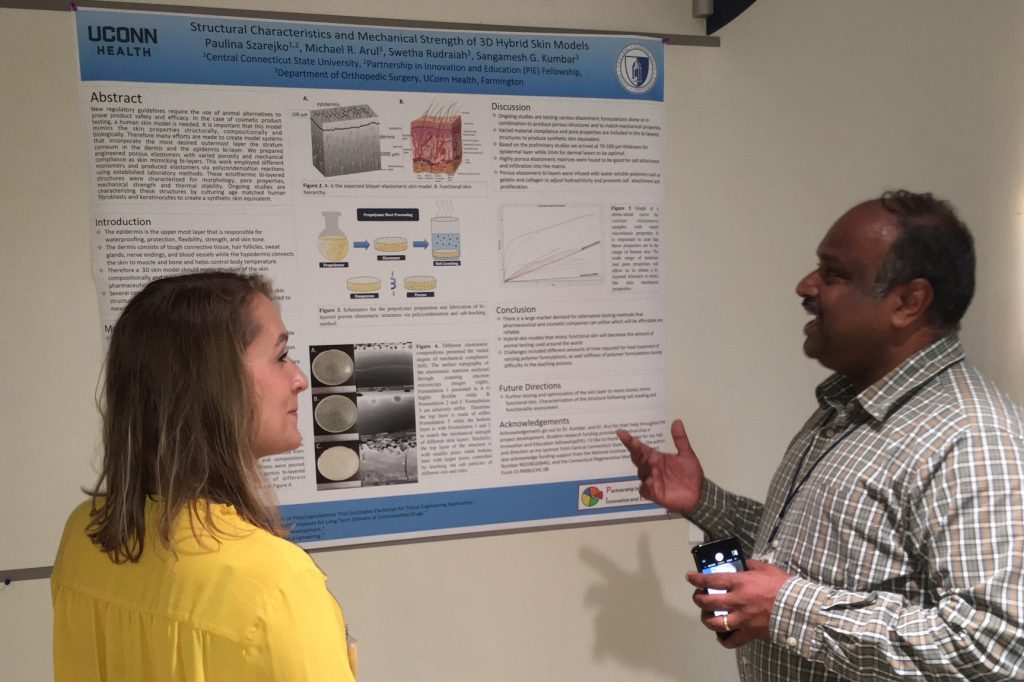 PIE Fellow Paulina Szarejko of Central Connecticut State University discusses her summer research project poster with her UConn Health mentor Dr. Sangamesh Kumbar, associate professor of orthopedic surgery and biomedical engineering at UConn Health. (Lauren Woods/UConn Health Photo)