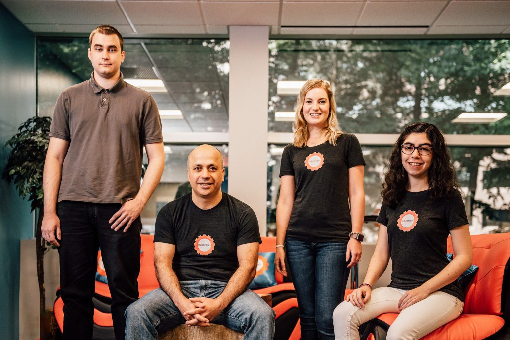 Peyman Zamani '95 (ENG), '06 MBA, CEO of Logicbroker Inc., seated, with, from left, Jordan Robidas '14 (ENG), Rebecca Kaelin '13 (CLAS), and Siena Biales '18 (CLAS, ENG). (Nathan Oldham/UConn Photo)