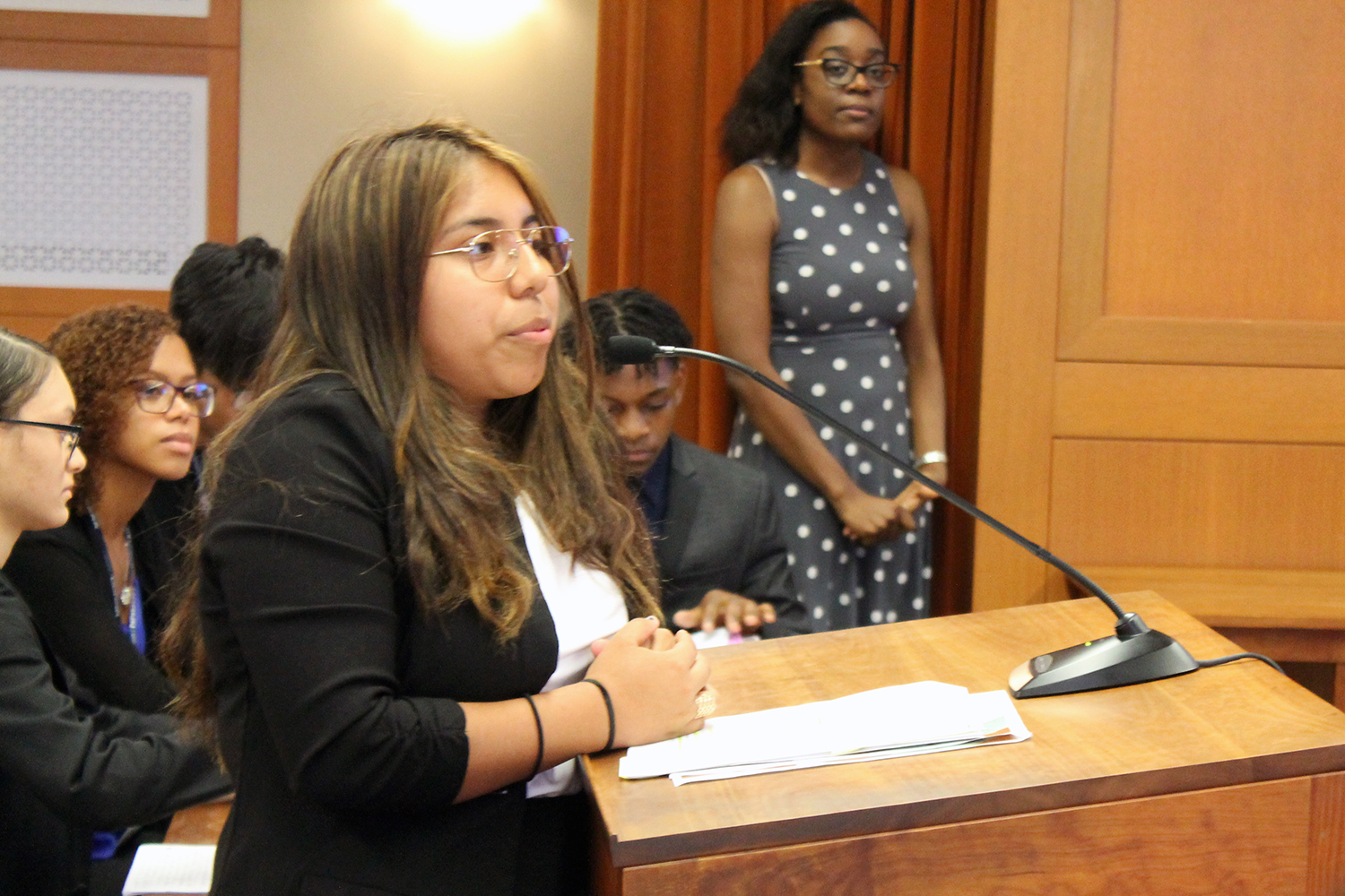 Hartford Public High School student Jasmine Jara presents the prosecution's case in a mock trial at UConn School of Law. In the background, from left, are fellow students, all members of the defense team, Frances Reyes, Dalice Gonzalez, Zam Khai, and Nick Simmonds, and a member of the teaching team, Alexandria McFarlane'18 JD.