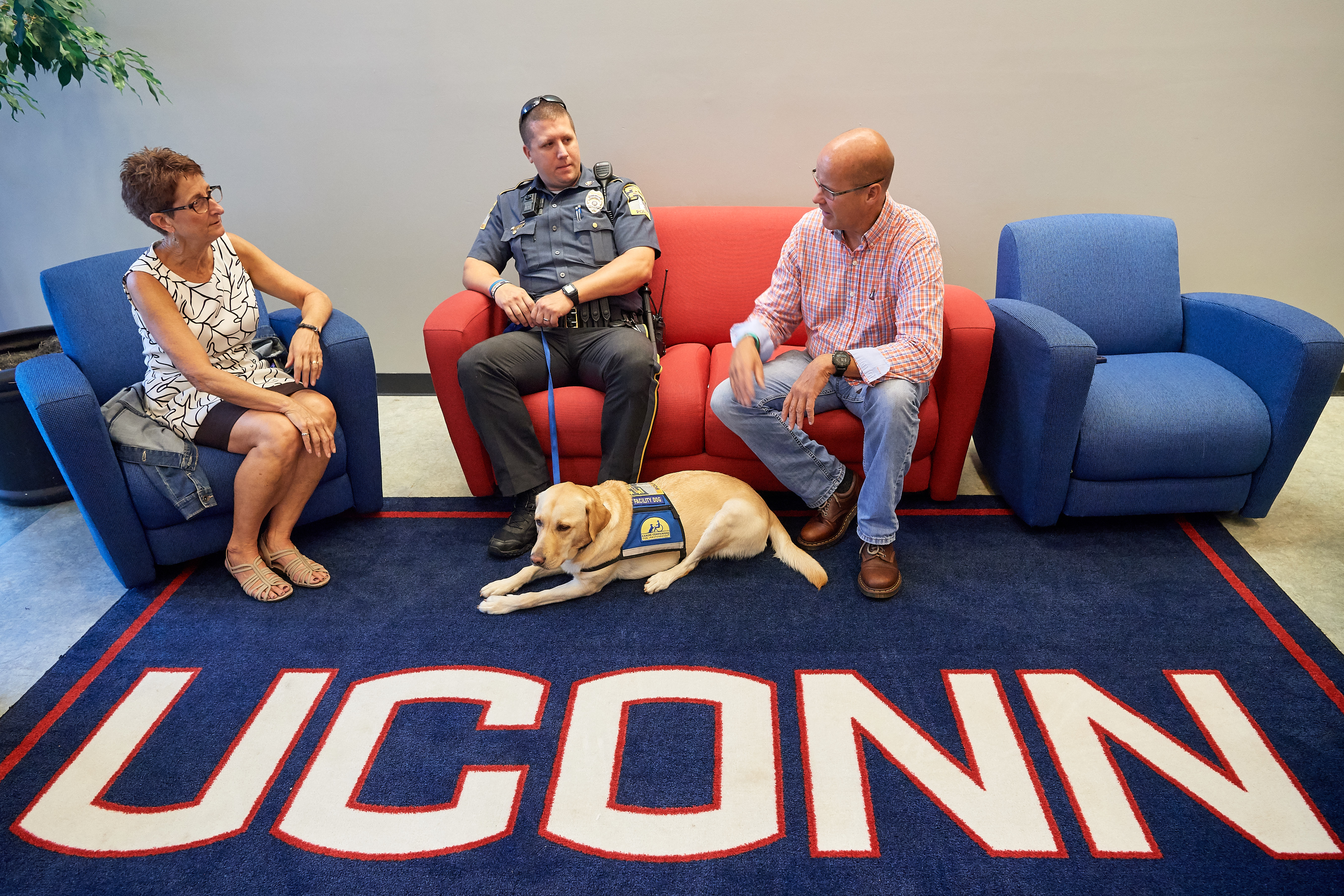 Sharon Mendes, left, with Officer Justin Cheney '07 (CLAS) and the police department's community outreach dog Tildy, and Paul Hanlon '15 (BGS), '17 MS, '19 MBA at the Student Union on Sept. 18, 2018. (Peter Morenus/UConn Photo)