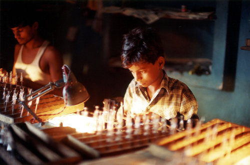 A young boy working at a light bulb factory in India. )Photo by Robin Romano/University Library Archives Special Collections)