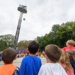 Students, teachers, and parents look on as UConn Firefighters atop a ladder truck drop eggs with protection created by students at Goodwin Elementary School in Mansfield on Sept. 21. (Peter Morenus/UConn Photo)