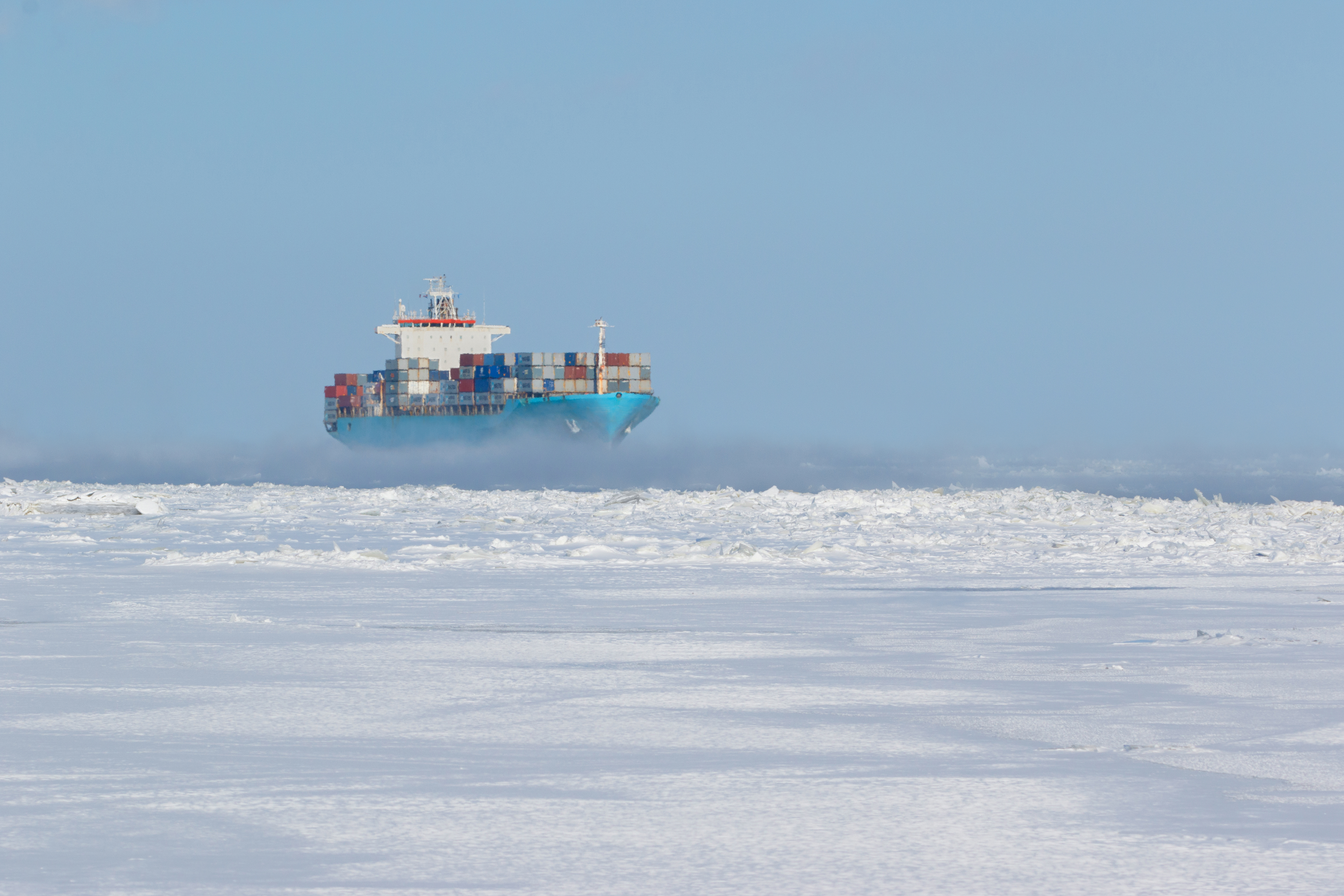 Large cargo filled with containers navigating through ice-surrounded passage. (Getty Images)