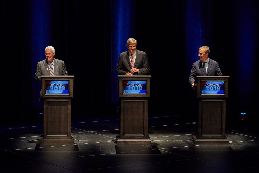Candidates Oz Griebel, left, Bob Stefanowski, and Ned Lamont laugh as the gubernatorial debate starts at the Jorgensen Center for the Performing Arts on Sept. 26, 2018. (Peter Morenus/UConn Photo)