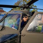 Abdullah Alsenan, a graduate student in the School of Business, left, steps out of a Sikorsky Black Hawk helicopter on the Student Union Mall during Lockheed Martin Day on Sept. 27, 2018. (Peter Morenus/UConn Photo)